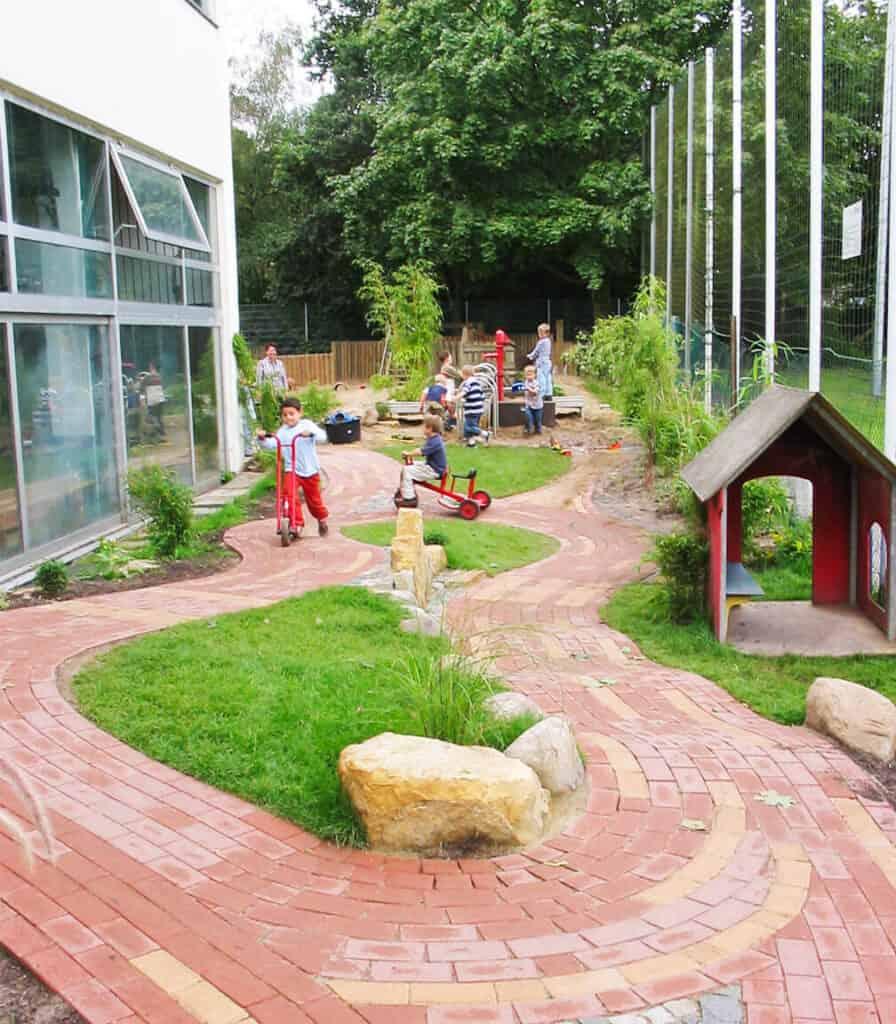 Kinder spielen auf einem Spielplatz mit gepflasterten wegen von Markus Stolze Garten- und Landschaftsbau GmbH